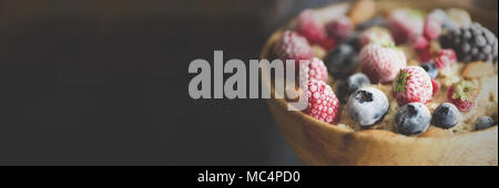 Oatmeal porridge with frozen berries, almonds in wooden bowl. Banner. Healthy breakfast. Clean eating, detox diet. Vegetarian, raw, vegan concept - Stock Photo