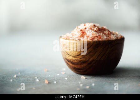 Pink Himalayan salt crystals and powder in wooden bowls on grey concrete background. Healthy diet without salt. Copy space - Stock Photo