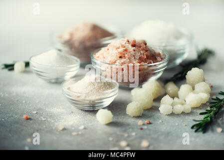 Mix of different salt types on grey concrete background. Sea salts, black and pink Himalayan salt crystals, powder, rosemary. Salt crystal balls from Dead sea. Copy space - Stock Photo
