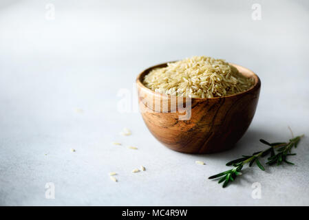 Raw organic brown rice in wooden bowl and rosemary on light concrete background. Food ingredients. Copy space - Stock Photo
