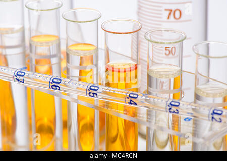 scientific experiment in chemistry laboratory with liquid in test tubes - Stock Photo