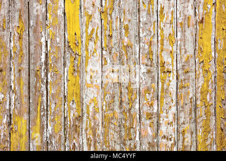 Rustic fence background painted with yellow paint, which is erased ...