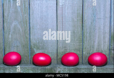 Red Easter eggs on rustic wooden fence background  Chicken eggs in red color and wooden fence - Stock Photo