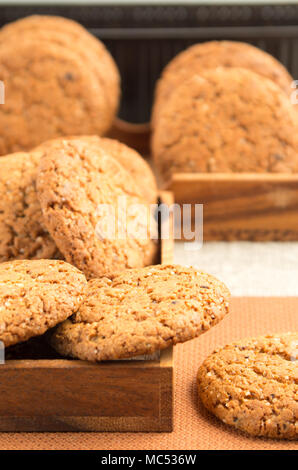 Many of oatmeal cookies in two wooden boxes on a brown fabric blur and shallow depth of field - Stock Photo