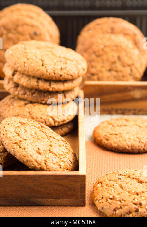 Group of oatmeal cookies in two wooden boxes on a brown fabric blur and shallow depth of field - Stock Photo