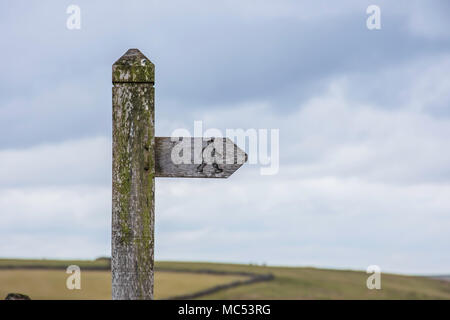 Wooden post covered with moss,direction sign for hiking tourists pointing at footpath.Green hills of England and cloudy sky in background. - Stock Photo