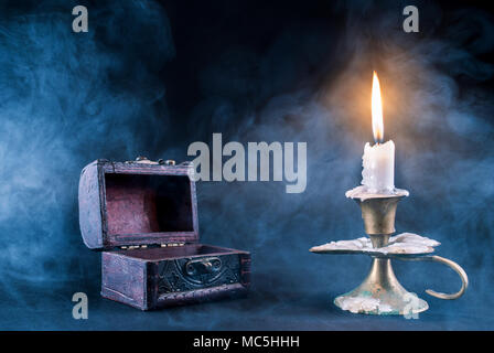 Candle in candlestick burning and old wooden box and on dark and smoked background. Halloween concept - Stock Photo