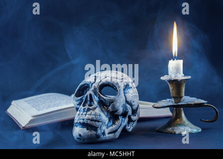 Gothic skull and candle in candlestick burning and book in background, dark and smoked scene. Halloween concept