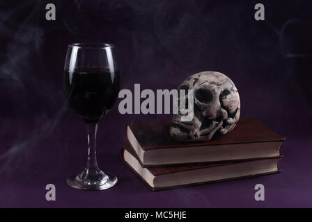 Skull on books and wine glass on purple dark and smoked background, Halloween concept, low key - Stock Photo