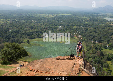 Couple taking a selfie with a selfie stick at Sigiriya Rock Fortress, Central Province, Sri Lanka, Asia. - Stock Photo