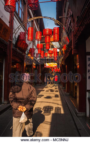 An old man walks through the bazaar part of the Yuyuan Gardens area of Shanghai. Shadows of red lanterns are cast around him. - Stock Photo