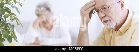 Close-up of a worried, elderly man deep in thoughts, with his hand on his forehead and a sad senior woman blurry in the background - Stock Photo