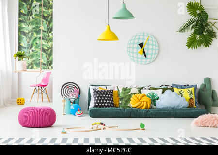 Pink pouf and kids' toys on the floor in bright playroom interior with many pillows on the couch