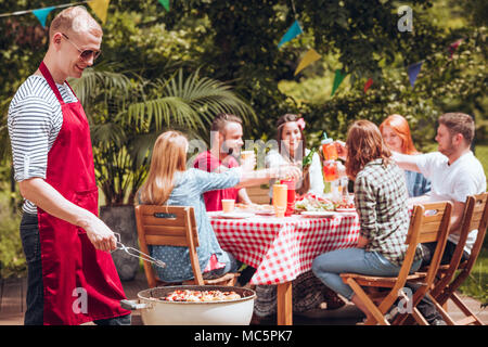 Happy man grilling during a birthday party in the garden during the summer - Stock Photo