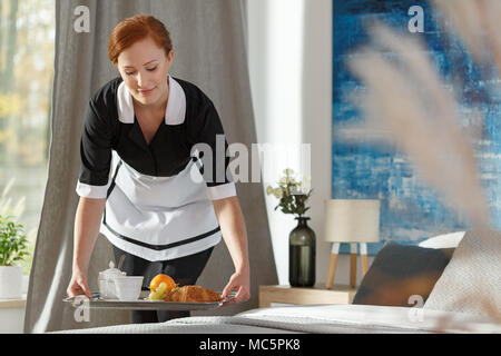 A young, ginger housemaid delivering breakfast to a hotel bedroom - Stock Photo