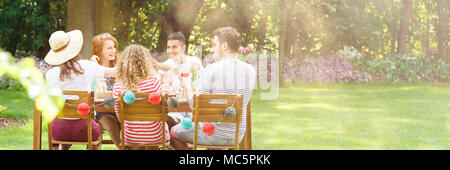 Panorama of happy friends eating lunch in the garden during a birthday party - Stock Photo