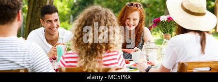 Panorama of smiling friends enjoying a garden party during sunny spring weather - Stock Photo
