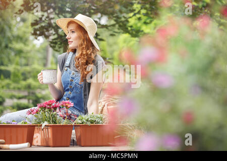 Pretty woman in straw hat on her head drinking tea on terrace, sitting next to containers with red flowers - Stock Photo