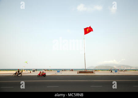 Cityscape of a city of Nha Trang with a red Vietnamese flag. Motorbikes driving along a beach road. Text on a flag socle: Square 2-4 - Stock Photo