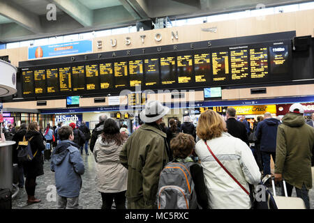 Euston Station crowd & back view of family standing waiting on the busy concourse looking at the departures board in London England UK    KATHY DEWITT - Stock Photo