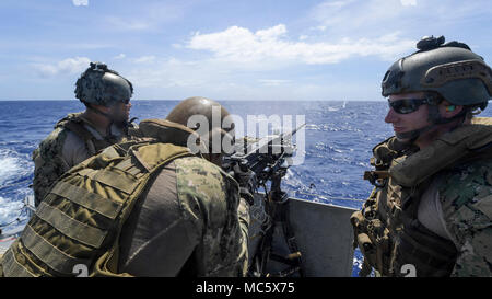 A Sailor assigned to Coastal Riverine Squadron (CRS) 4, Det. Guam fires an M2 machine gun aboard a Mark VI patrol boat during a crew-served weapons qualification in the Philippine Sea, April 12, 2018. CRS-4, Det. Guam, assigned to Costal Riverine Group 1, Det. Guam, is capable of conducting maritime security operations across the full spectrum of naval, joint and combined operations. Further, it provides additional capabilities of port security, embarked security, and theater security cooperation around the U.S. 7th Fleet area of operations. (U.S. Navy Combat Camera photo by Mass Communication - Stock Photo