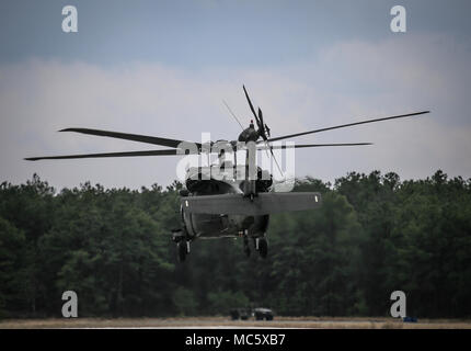 A New Jersey Army National Guard UH-60L Black Hawk helicopter from Det. 2 , C Company, 1-171st Aviation lifts off for rescue basket training over Joint Base McGuire-Dix-Lakehurst, N.J., April 11, 2018. The New Jersey Army National Guard trained with New Jersey Task Force One, an urban search and rescue unit. (U.S. Air National Guard photo by Master Sgt. Matt Hecht) - Stock Photo