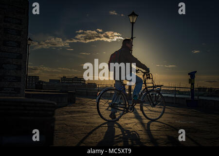Silhouette of a Cyclist at Sunset in Old Portsmouth - Hampshire, UK - Stock Photo