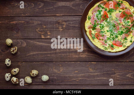 Omelet with sausage and fresh tomatoes and herbs on a clay plate and quail eggs. The top view. Breakfast - Stock Photo