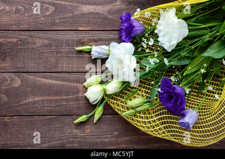 Freshly picked white and purple flowers eustomy (lisianthus) in the form of a bouquet on the wooden background. The top view. - Stock Photo