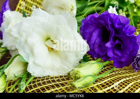 Freshly picked white and purple flowers eustomy (lisianthus) in the form of a bouquet on the wooden background. Close up - Stock Photo