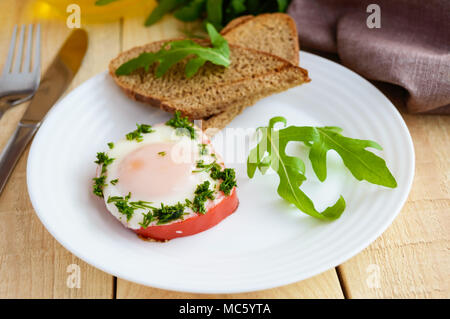 Scrambled eggs, baked in a ring bell pepper, toast, arugula leaves. Light breakfast. - Stock Photo