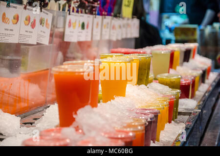 Fruits juices iced and on display for sale at a market stall at La Bocqueria n Barcelona. - Stock Photo