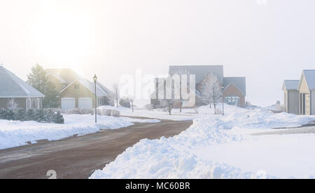 Fog rolling in on a North American residential neighborhood in winter. - Stock Photo