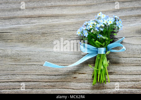Small bouquet of blue forget-me-not flowers, tied with a blue ribbon, on the background of old wooden plank, with copy-space - Stock Photo