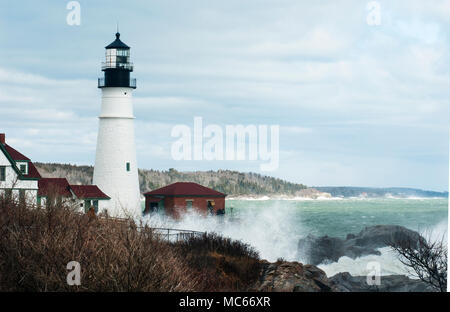 High surf from rare astronomically high tides break over rocks by Portland lighthouse in Maine. - Stock Photo