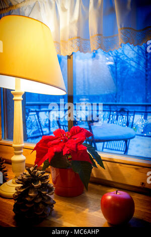 Warm lamp and xmas decorations on a windowsill, with winter landscape seen through the window. - Stock Photo