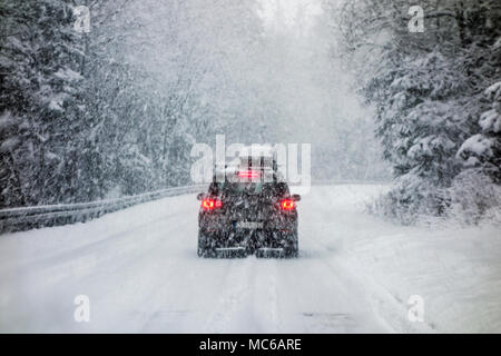 Car driving during winter snow taken through a windshield covered with snowflakes. - Stock Photo