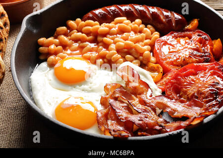 English Breakfast with sausages, grilled tomatoes, egg, bacon and beans on frying pan. - Stock Photo