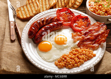 English Breakfast with sausages, grilled tomatoes, egg, bacon, beans and bread on white plate - Stock Photo