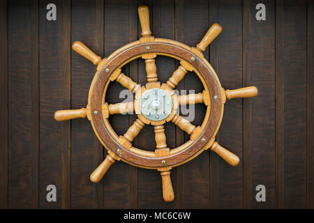 Wooden metal old wheel steering on wood background. - Stock Photo