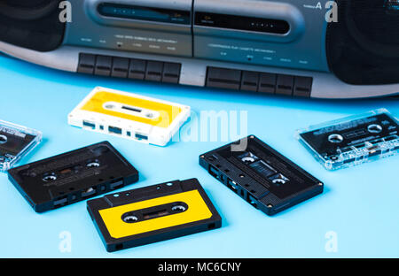 Old black retro cassette music audio tape recorder and retro cassette tape collection on blue background - Stock Photo