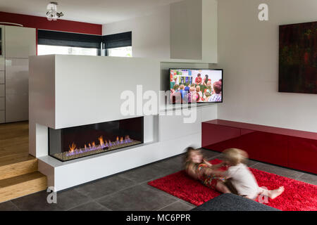 Two children playing on floor by fireplace with television on, blurred motion - Stock Photo