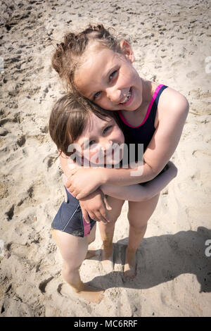 Portrait of a two smiling sisters hugging each other at the beach. - Stock Photo