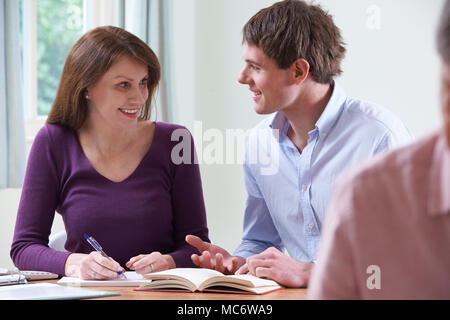 Mature Woman With Tutor In Adult Education Class - Stock Photo