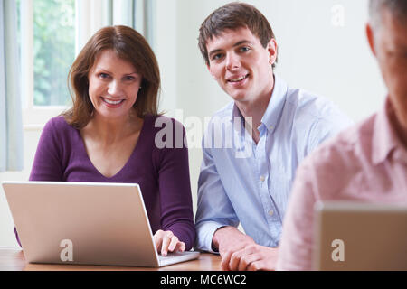 Portrait Of Mature Woman With Tutor In Adult Education Class - Stock Photo