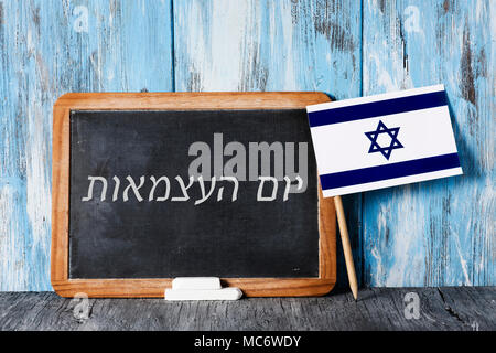 a wooden-framed chalkboard with the text independence day written in hebrew in it, some pieces of chalk and an israeli flag on a rustic wooden surface - Stock Photo
