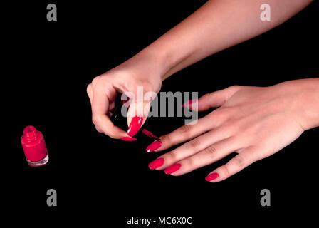 Girl applying red nail polish on black background - Stock Photo