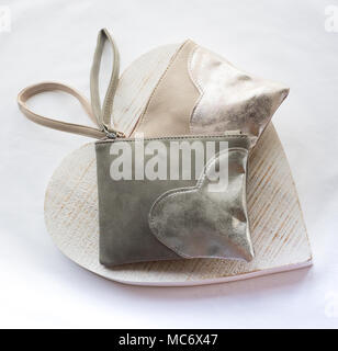 Pale pastel coloured cloth purses in grey and peach with applied heart motifs set on a wooden cream heart shape and white background - Stock Photo