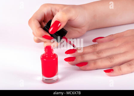 Young girl applying red nail polish gel herself on white background with brush, close up - Stock Photo