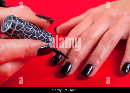 Women applying black nail polish gel herself on red background with brush, close up - Stock Photo